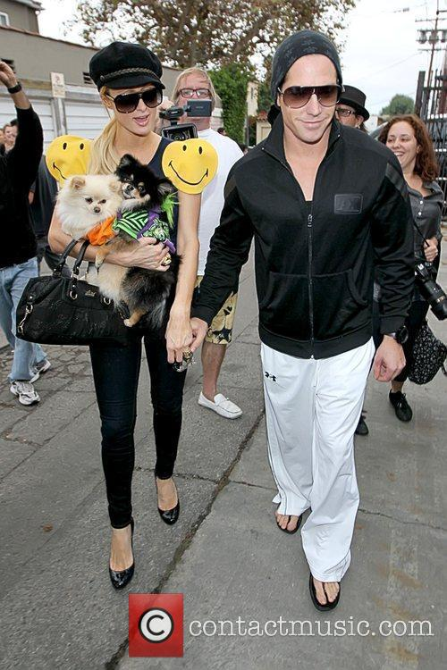 Paris Hilton, holding her dogs that are dressed...
