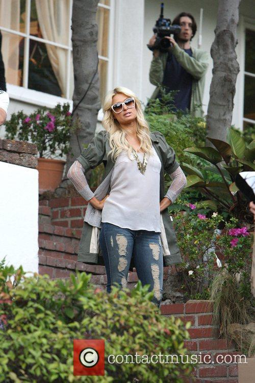 Paris Hilton in tight ripped jeans and leopard...
