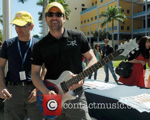 Patrick Dempsey with an electric guitar prior to...