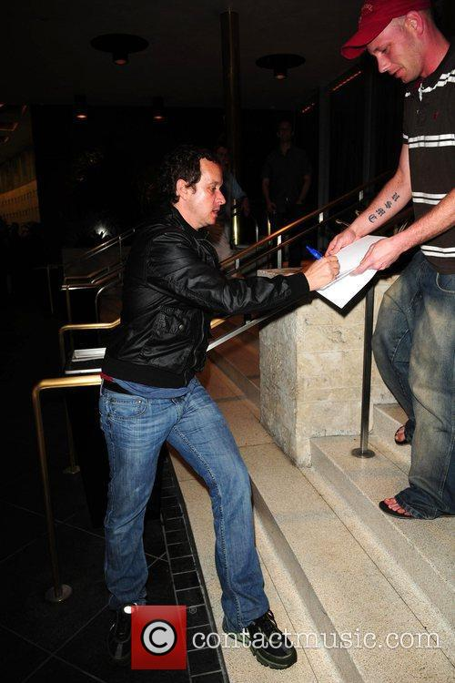 Signs autographs for fans while on a night...