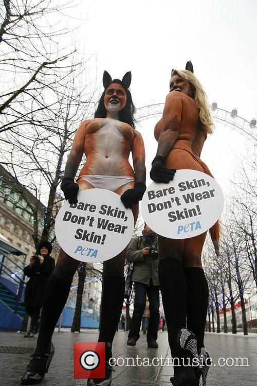 PETA protesters, holding signs stating 'Bare Skin, Don't...