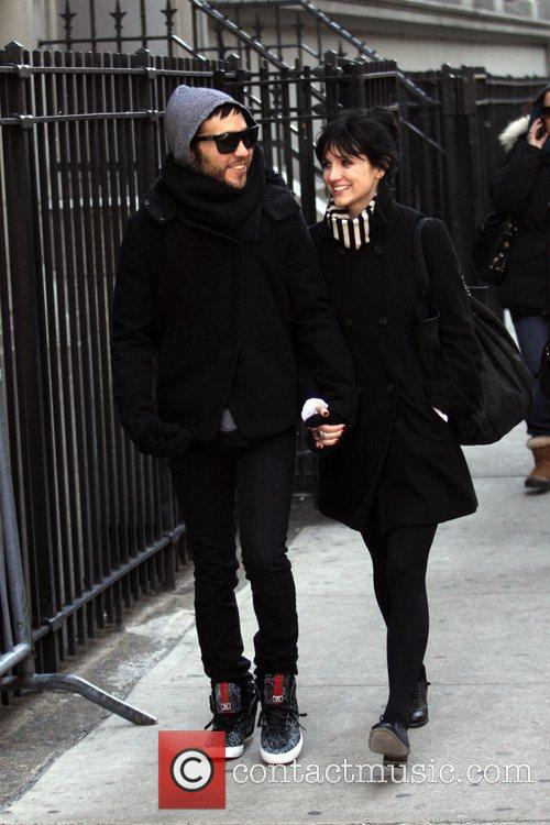 Hold hands as they walk through Soho together.