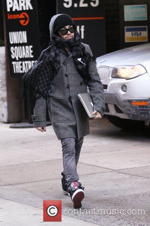 Pete Wentz, carrying an Apple MacBook, walking in...