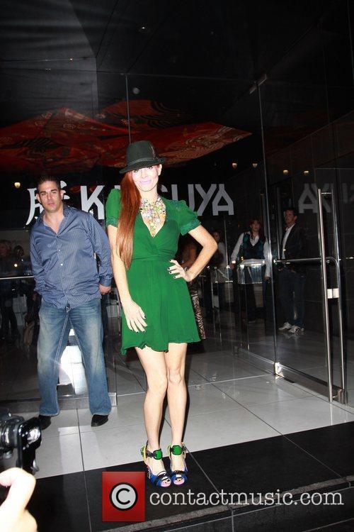 Poses for photographers as she leaves katsuya Restaurant.