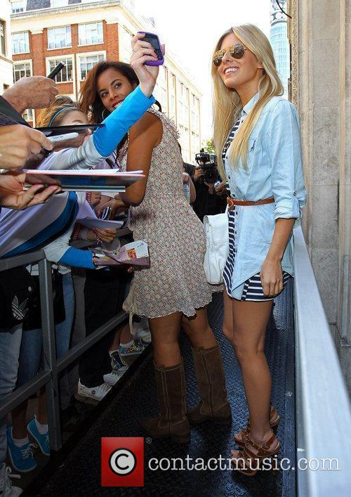 Sign autographs for fans as she arrives at...