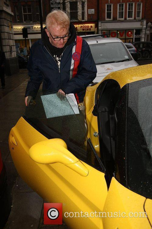 Chris Evans getting into his yellow Ferrari outside...