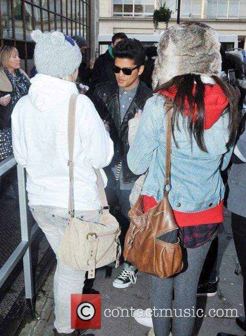 Bruno Mars signs autographs for fans  as...