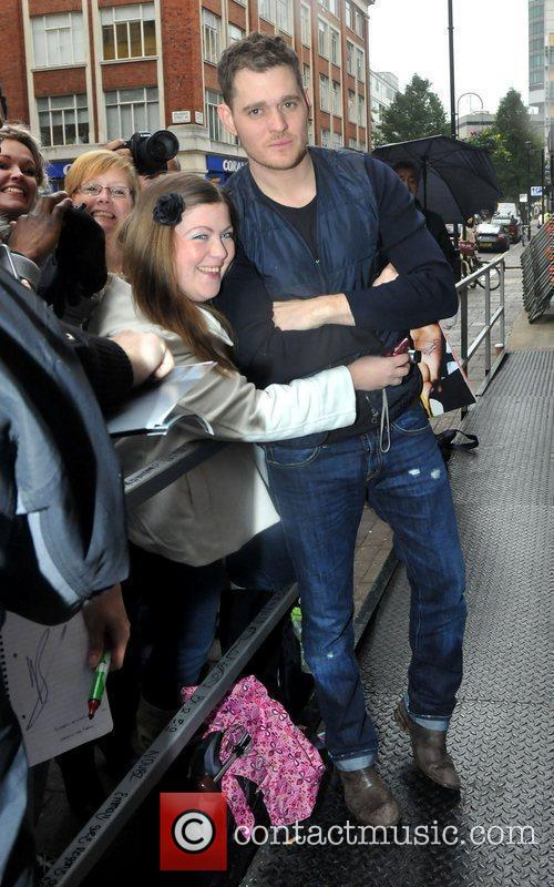 Poses with a fan as he arrives at...