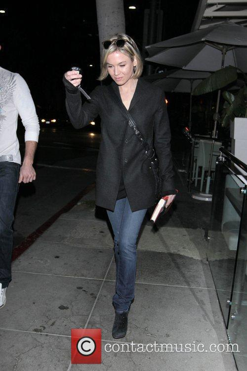 Renee Zellweger walks back to her car surrounded...
