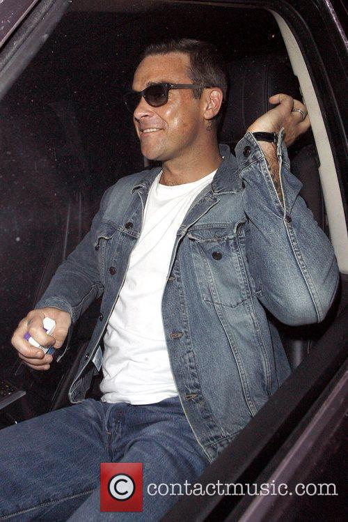 Robbie Williams wearing a denim jacket and jeans...