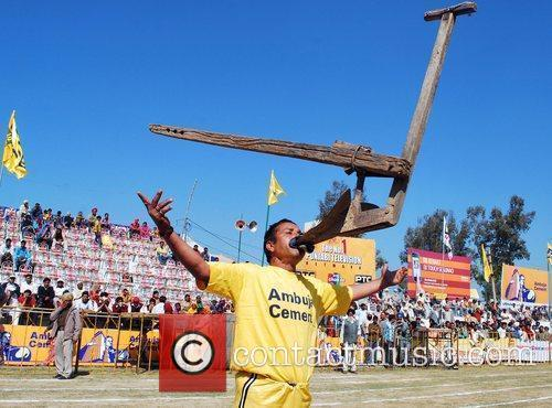 An Indian villager holds up a plough in...