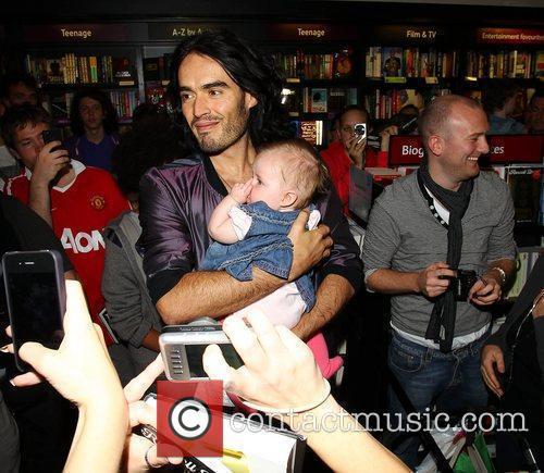 Russell Brand cuddles a baby as he visit's...