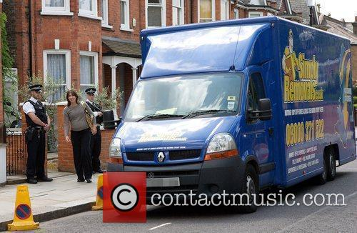 Leaving her house as removal men prepare to...