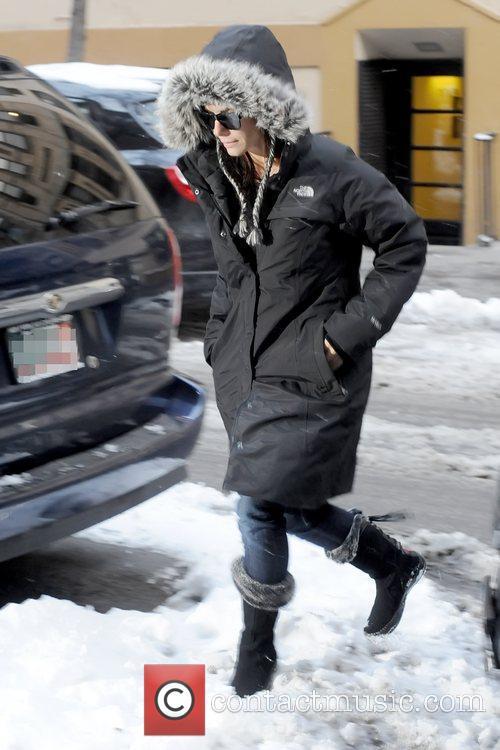 Sandra Bullock walks over snow as she arrives...