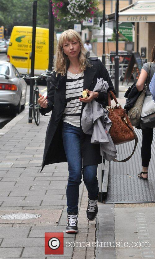 Sara Cox eating an apple as she leaves...
