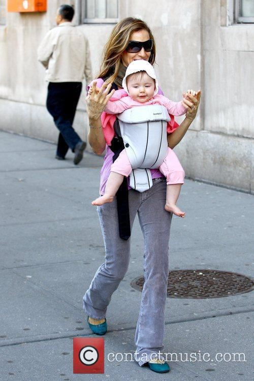 Carrying one of her baby twin daughters, who's...