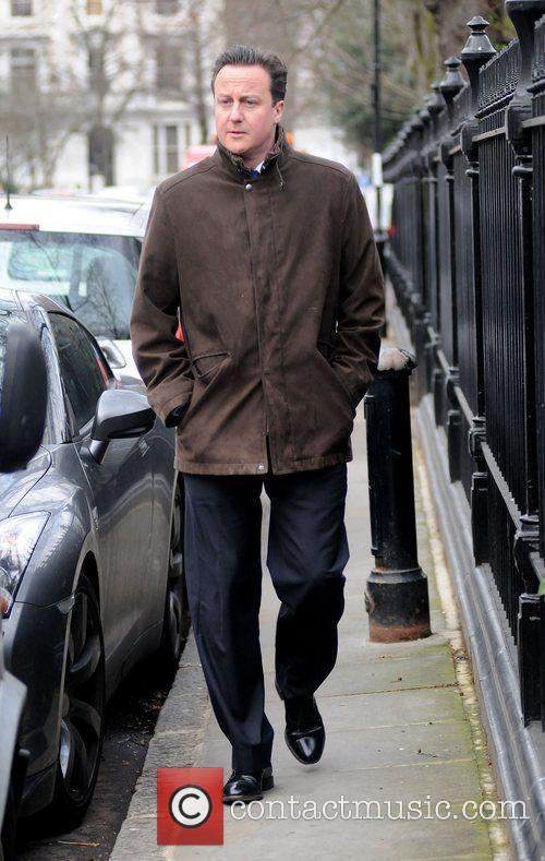 David Cameron makes his way home after taking...