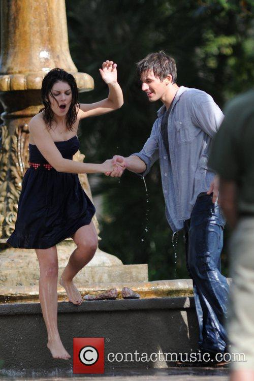 Shenae Grimes falls in a fountain with a...