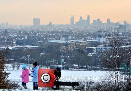 Children enjoy the snow on Hampstead Heath with...