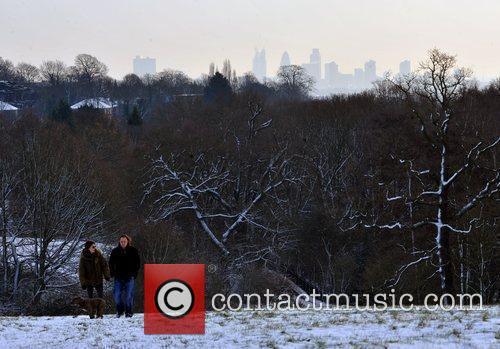 People walk through snowy Hampstead Heath with the...