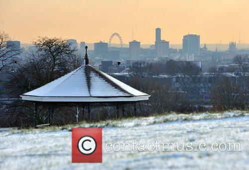 Snow covers the grass on Hampstead Heath with...
