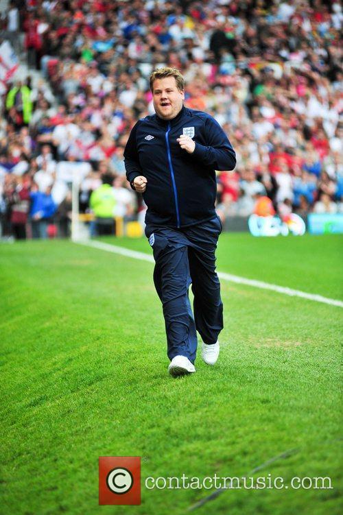 James Corden runs back to the bench during...