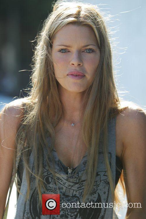 Sophie Monk with her new brown hair, carries...
