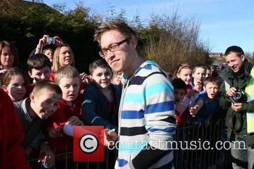 Signs autographs at a Primary School while taking...