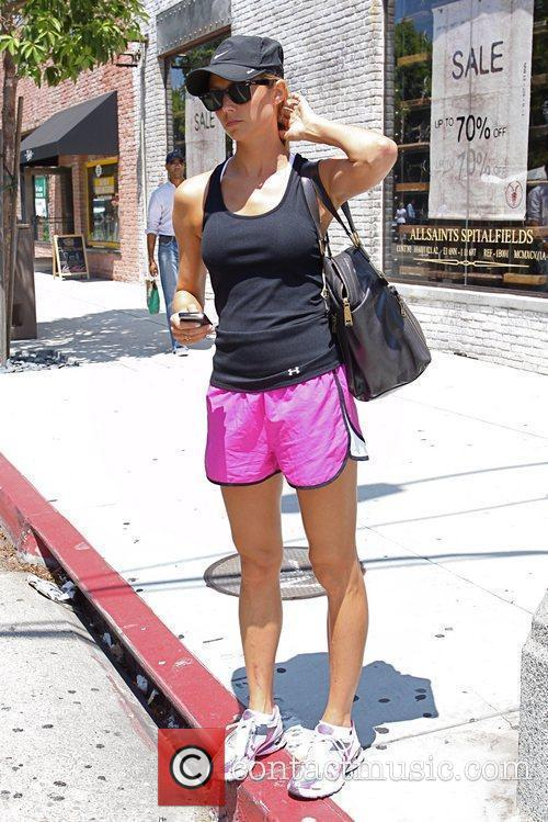 Stacy Keibler wearing pink shorts and a black...