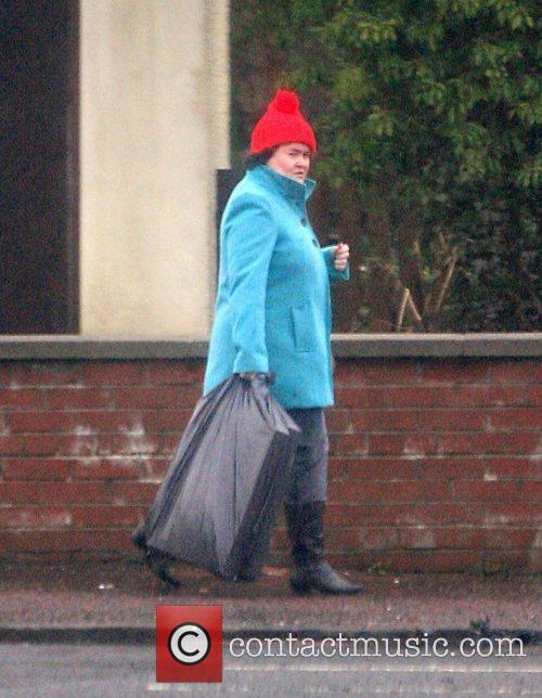 Susan Boyle, carrying a black sack outside her...