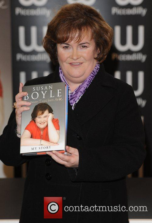 Signs copies of her autobiography 'The Woman I...