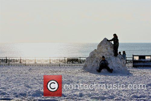 Children play in the snow by the sea...