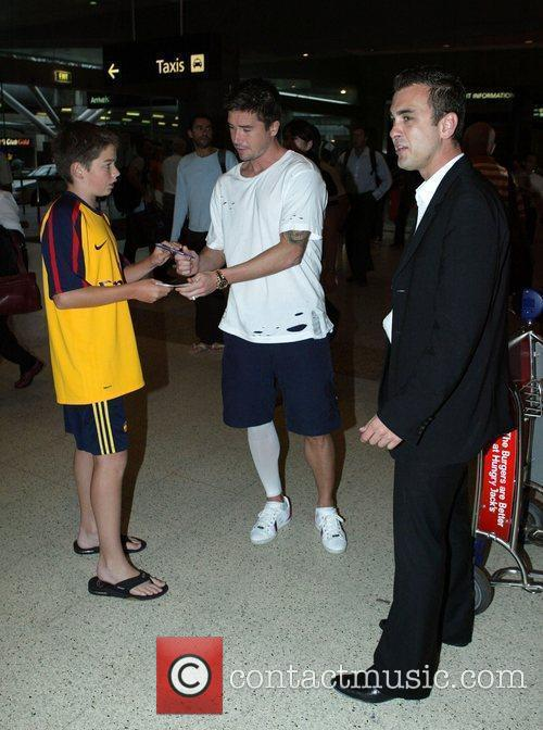 Harry Kewell signs autographs for fans as he...