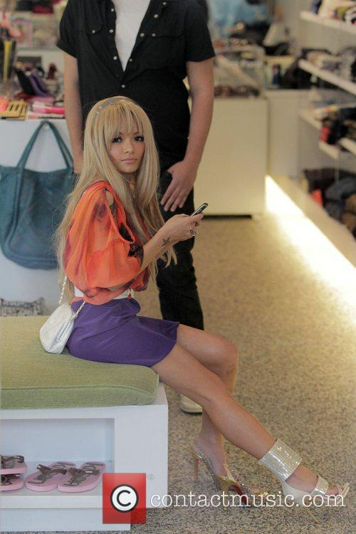 Tila Tequila trying on shoes at shop on...