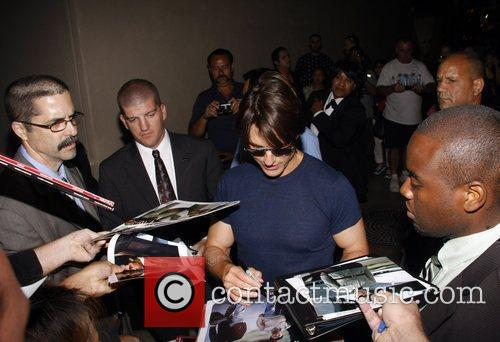 Tom Cruise signs autographs as he leaves the...