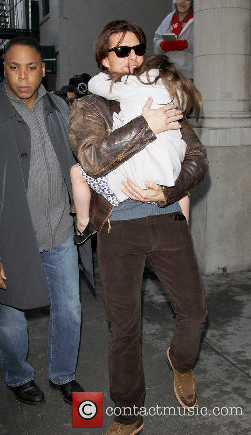 Tom Cruise carries his daughter Suri Cruise whilst...