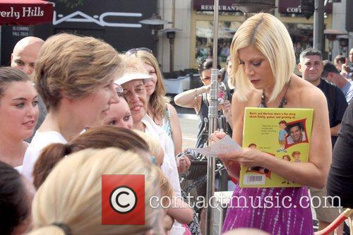 Tori Spelling signing autographs for fans Tori Spelling...