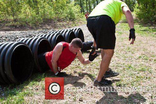 A Tough Mudder Participant Helps A Friend Get Through The 'boa Constrictor' Section Of The Course. 8