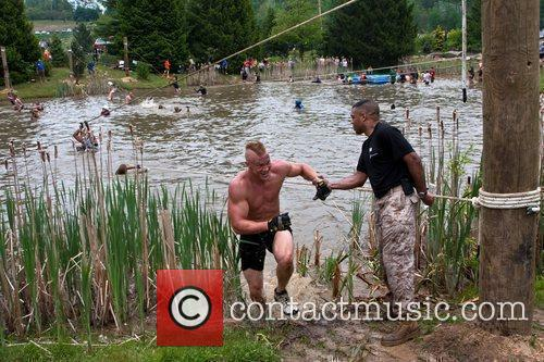 A Tough Mudder participant is helped out of...