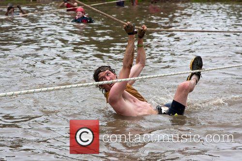 A Tough Mudder participant pulls himself through the...