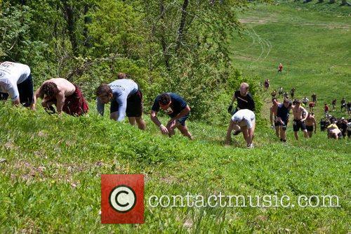 Tough Mudder participants climb to the top of...