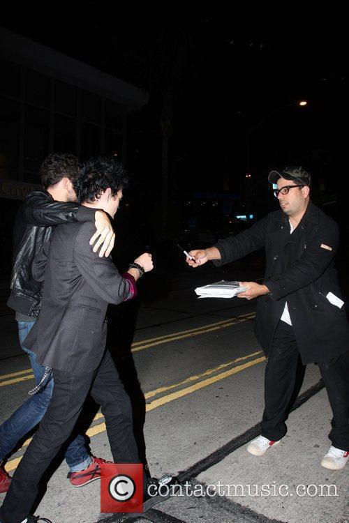 Deryck Whibley signing an autograph while leaving Trousdale...