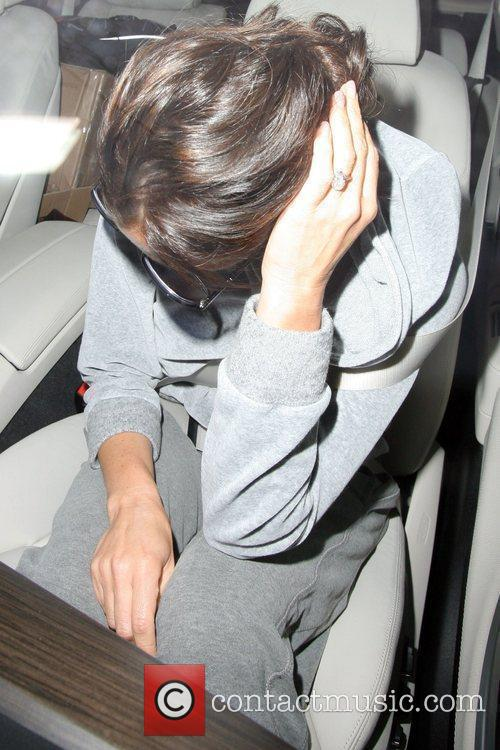 Hides her face as she gets into the...