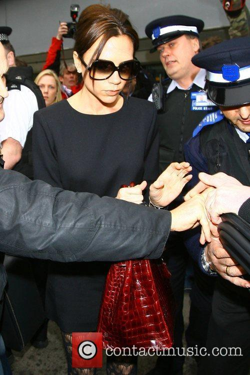Victoria Beckham arriving at Heathrow airport carrying a...