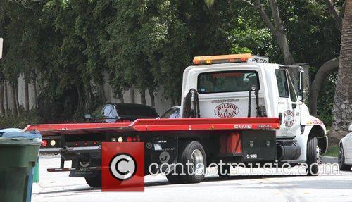 A tow truck tows Victoria Beckham's signature Porsche...