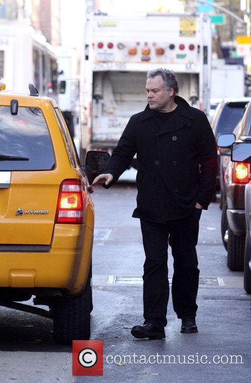 Walks onto the street to hail a cab...