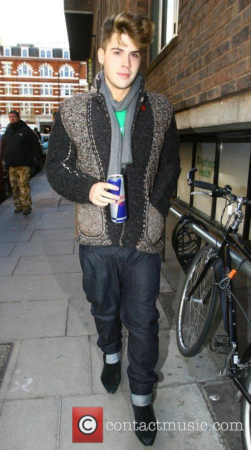 X Factor finalist Aiden Grimshaw carrying a Red...