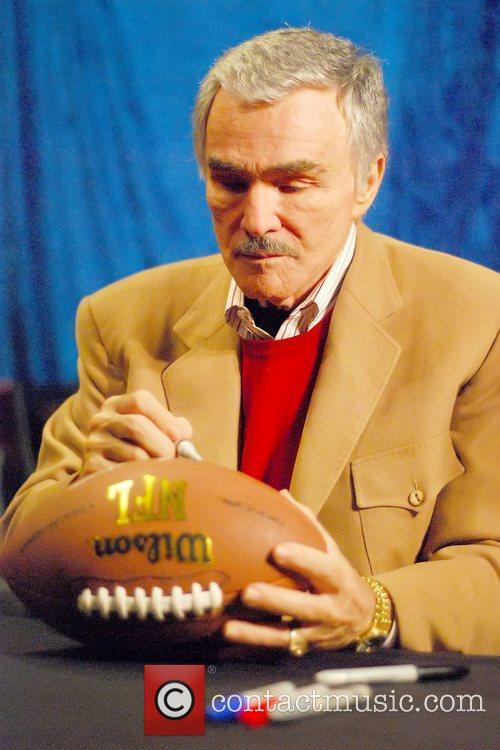 Burt Reynolds signs a football during a special...