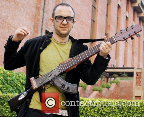 Poses with his AK-47 gun-guitar. The guitarist will...
