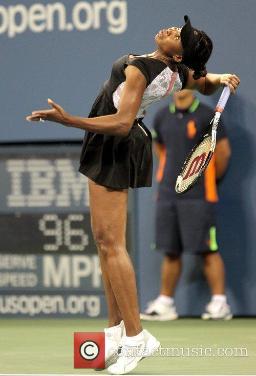 Venus Williams makes a serve during her match...